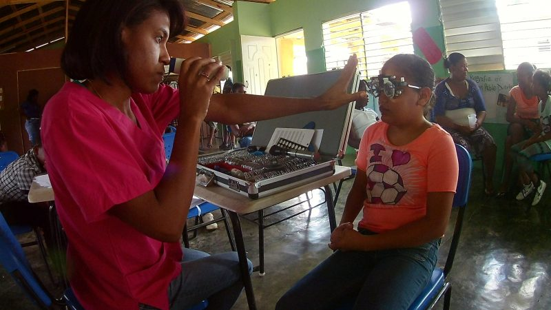 eye doctor checking girl in Bonao village