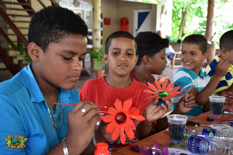 boy painting plastic flower on ranch in Anamuya