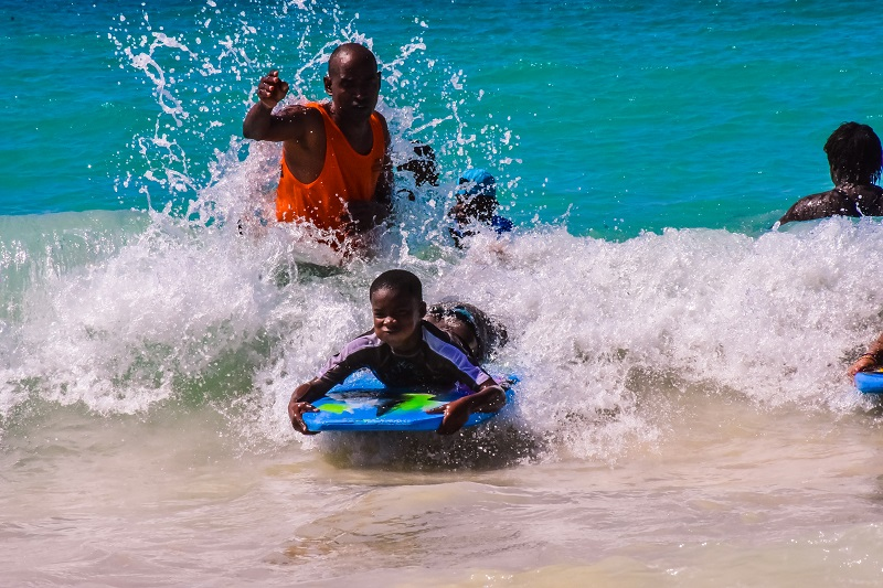 guide and children boogie boarding at Macao Beach
