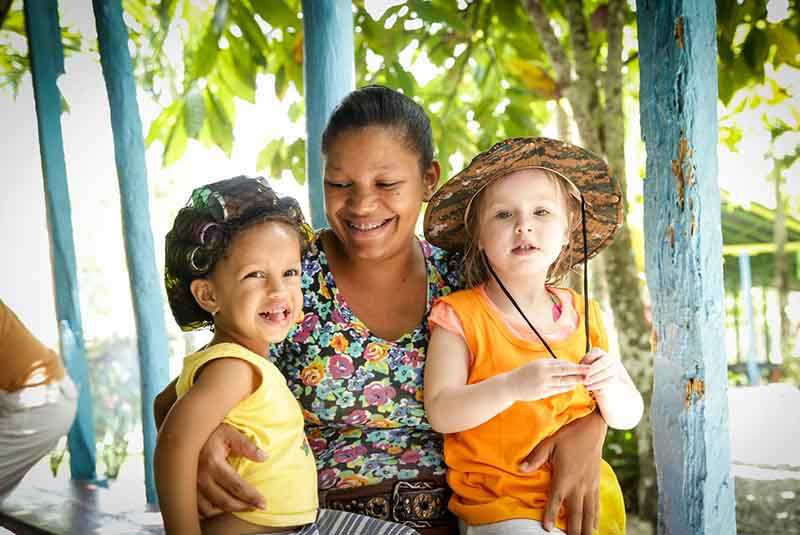 smiling local women and girl with foreign girl in Anamuya - Dominican Republic