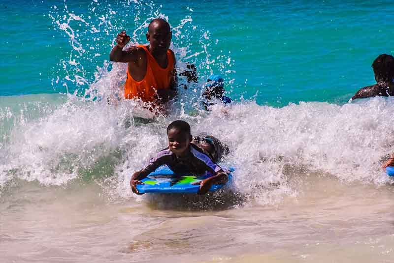Guide helping children to boogie boards in Macao - Punta Cana