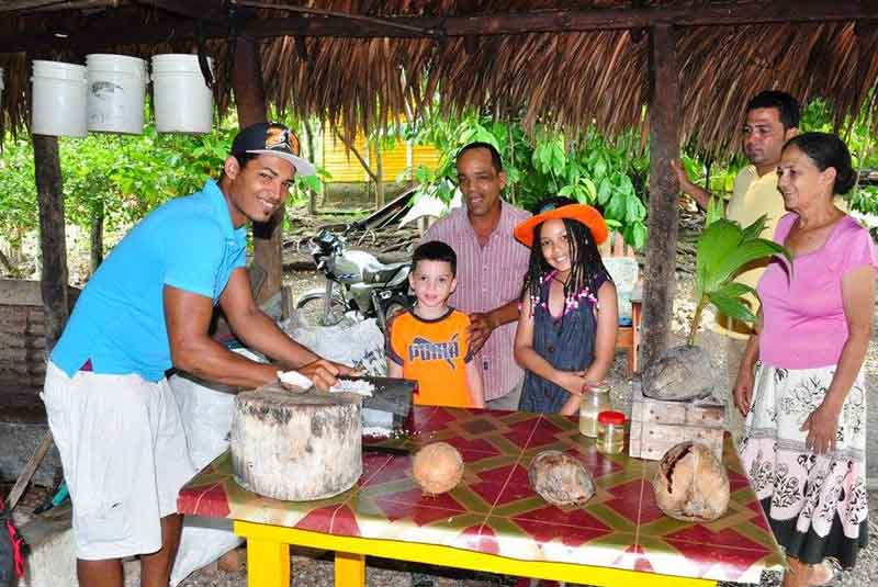 family visits coconut farmer to see process of coconut oil making