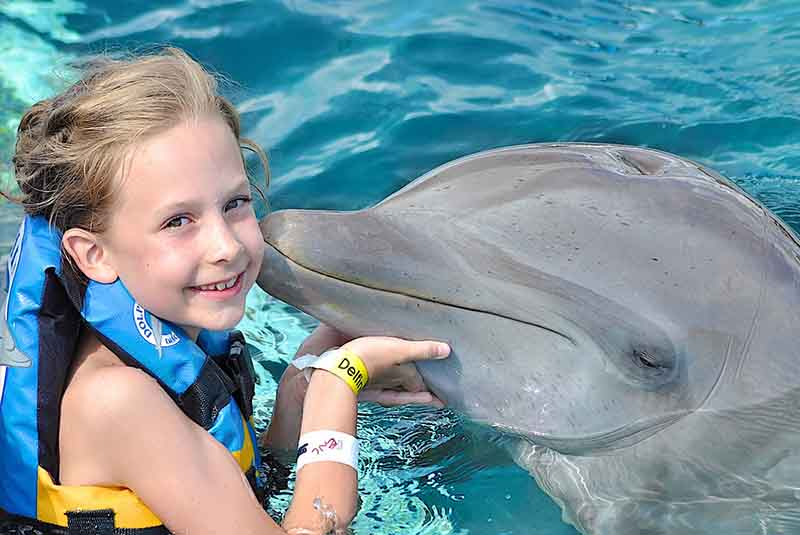 Girl receiving kiss by dolphin in Punta Cana - Dominican Republic