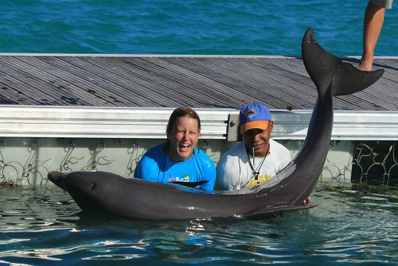 women interacting with dolphin and trainer in Punta Cana -Dominican Republic