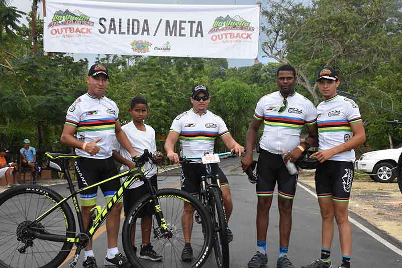 team posing for picture in front of start and finish line of mountain bike comptetition in Punta Cana - Dominican Republic
