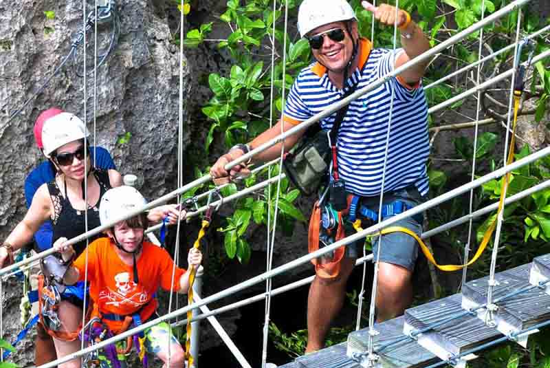 father and son in ziplining gear climbing stairs in Cap Cana - Dominican Republic
