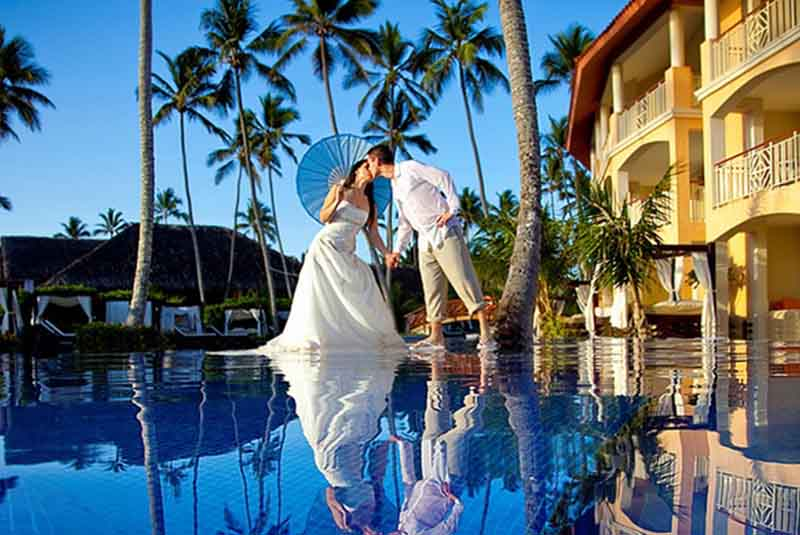 wedding couple posing for picture on pool in Majestic Colonial in Punta Cana