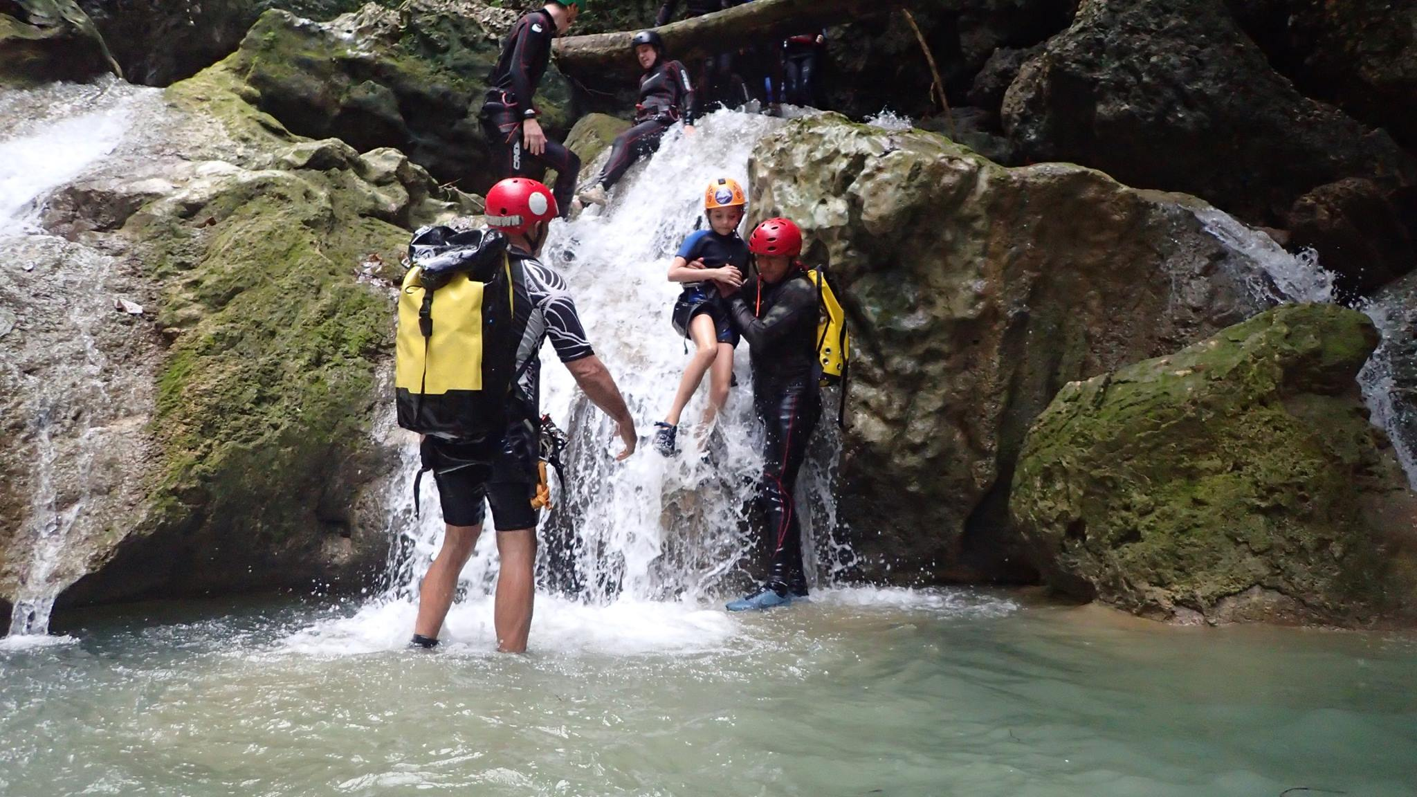 guides assisting boy on canyoning tour in Jarabacoa - Dominican Republic