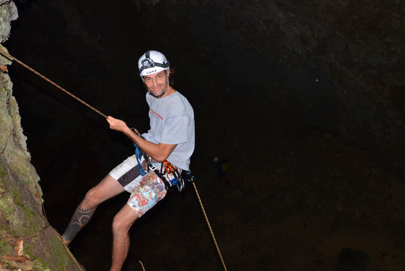 man rappeling down into cave in Cabarete - Dominican Republic