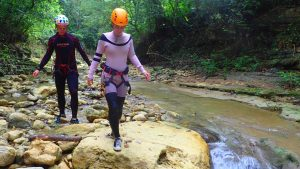 couple wearing safety equipment walking at river bed in Jarabacoa - Dominican Republic