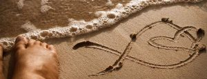 infinity sign with heart in sand with feet in water - Dominican Republic