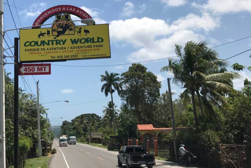 street sign to country world for zip lining tours in Puerto Plata