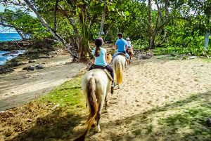 family with children riding horses at beach in Sosua - Dominican Republic