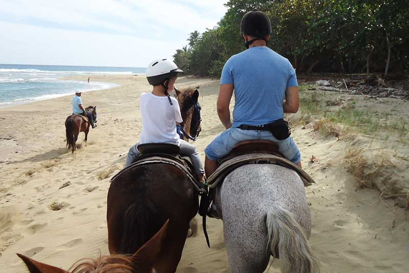 father and sun enjoying guided horse back riding tours in Sosua - Dominican Republic