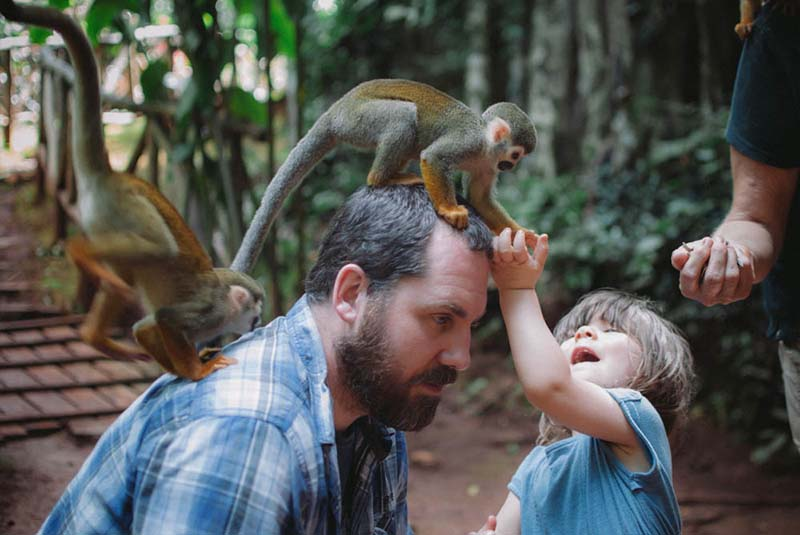 boy feeding squirrel monkeys in Puerto Plata's Monkey Jungle