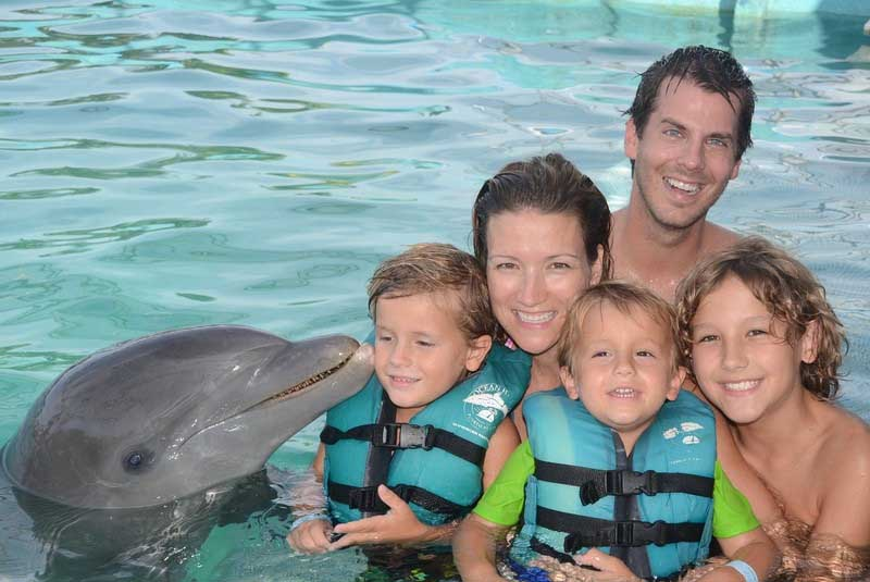 family posing with dolphin as part of dolphin tours in Ocean World in Puerto Plata