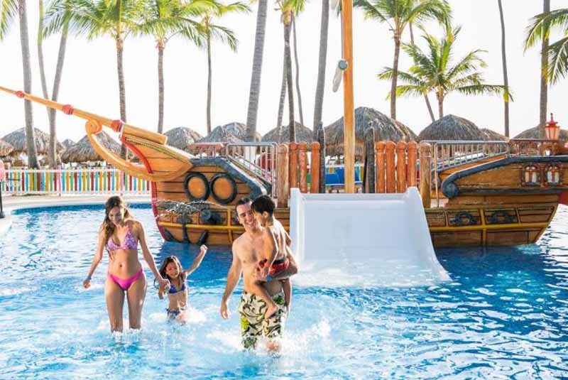 family with children at hotel pol with pirate ship slides in Punta Cana - Dominican Republic