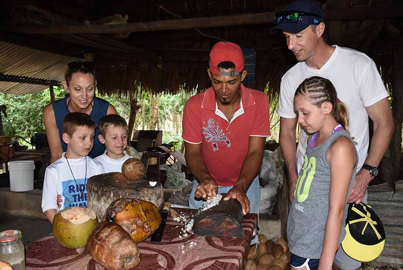 family watching local artisan grinding coconut - Outback Adventures Punta Cana
